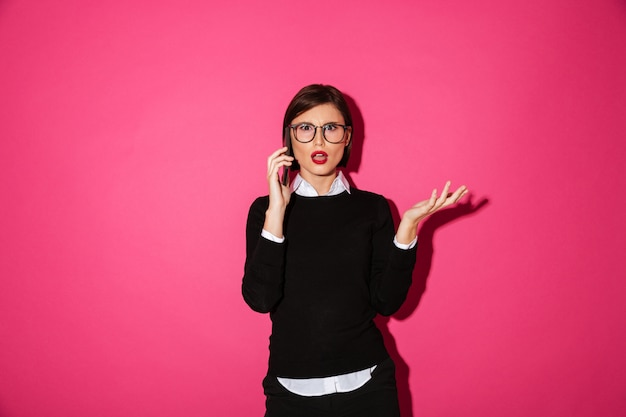 分離されたスマートフォンで話している不機嫌な若い女性 無料写真