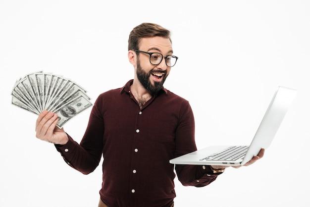 Шокирован молодой человек, держащий деньги и портативный компьютер. Бесплатные Фотографии
