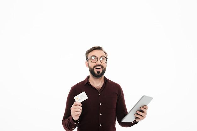 タブレットコンピューターを保持している幸せな陽気な男の肖像 無料写真