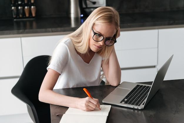 Молодая сосредоточенная дама работая дома с компьтер-книжкой и тетрадью Бесплатные Фотографии