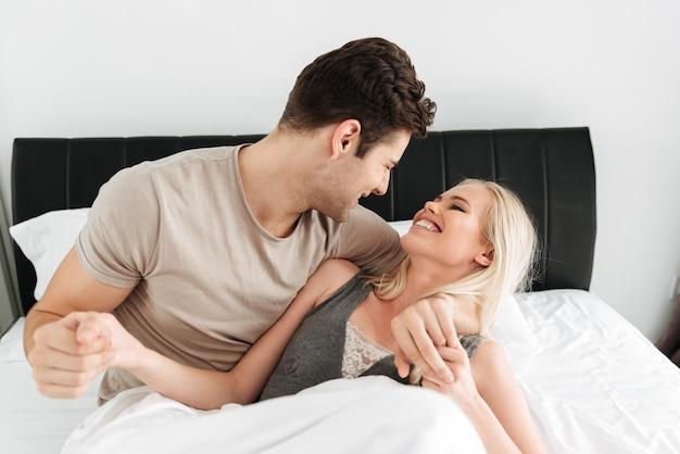 幸せな男と女のベッドで横になっているとハグ 無料写真