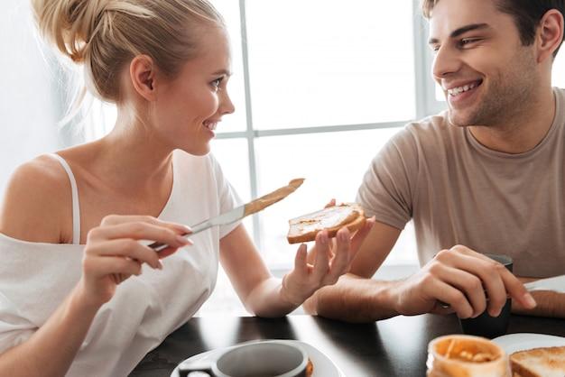 きれいなカップルがキッチンで朝食をとる 無料写真