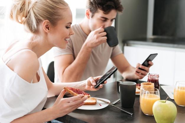 キッチンで朝食をとりながら、スマートフォンを使用してかなり集中している恋人 無料写真