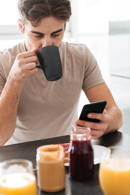 お茶を飲むと、スマートフォンを使用して焦点を当てた若者の肖像 無料写真