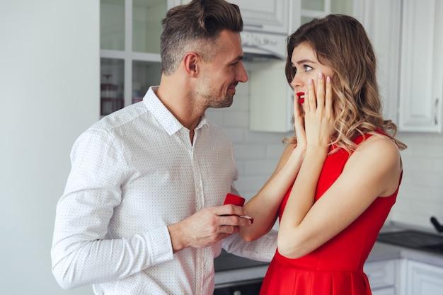 自宅で彼のガールフレンドに婚約指輪を与える若いハンサムな男 無料写真