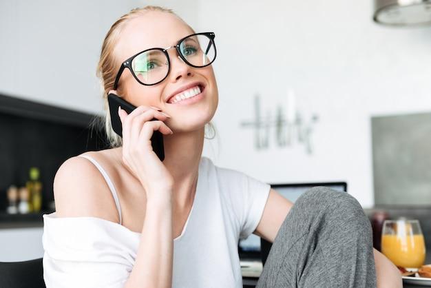 笑みを浮かべて、キッチンでスマートフォンで話しているメガネの陽気な女性 無料写真