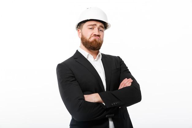Прохладный бородатый деловой человек в защитном шлеме, держа скрещенные руки Бесплатные Фотографии