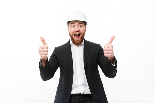 Веселый бородатый деловой человек в защитном шлеме показывает палец вверх Бесплатные Фотографии