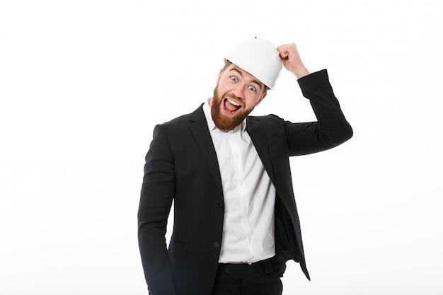 Счастливый бородатый деловой человек в защитном шлеме стучит в него Бесплатные Фотографии