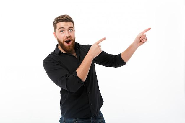 先に指しているシャツで驚く幸せなひげを生やした男 無料写真