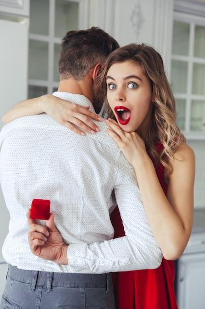 彼女の夫の手に婚約指輪を持つボックスを見て驚く女性 無料写真