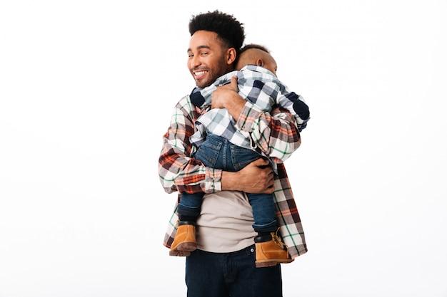 彼の幼い息子を抱いて幸せなアフリカ人の肖像画 無料写真