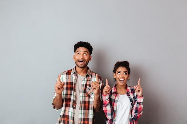 指で上向きに興奮して若いアフリカカップルの肖像画 無料写真