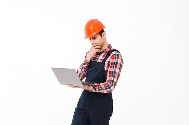 Портрет задумчивой молодой мужской строитель работает Бесплатные Фотографии