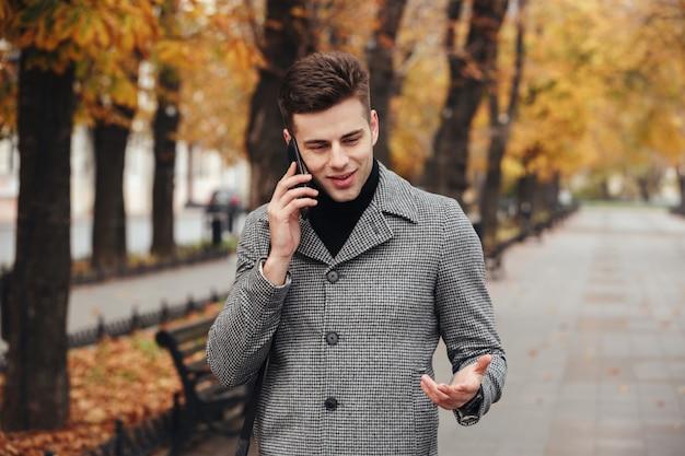 秋の木々と空の公園を歩いて、スマートフォンで話しているコートでエレガントな男性の写真 無料写真