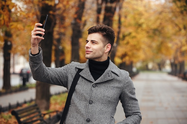 Жизнерадостный мужчина в пальто фотографирует природу или делает селфи с помощью черного смартфона, гуляя по бульвару Бесплатные Фотографии