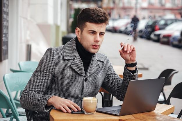 外のカフェに座って、タバコを吸って、カプチーノを飲んで陰気な表情でエレガントなビジネスマンの写真 無料写真