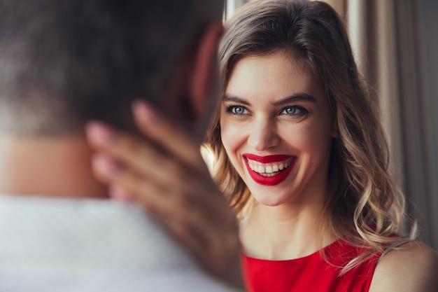 笑う女性の肖像画は彼女の夫を自宅で抱擁します。 無料写真