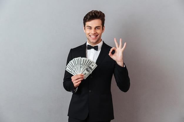 お金を保持している幸せな若い男。 無料写真