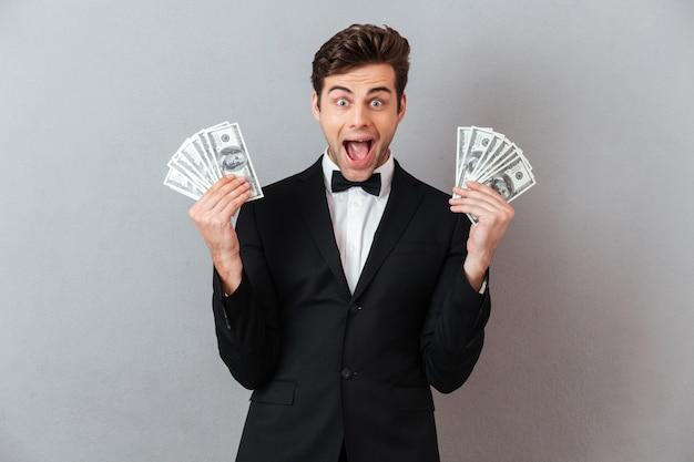 お金を保持しているハンサムな男を叫んでください。 無料写真