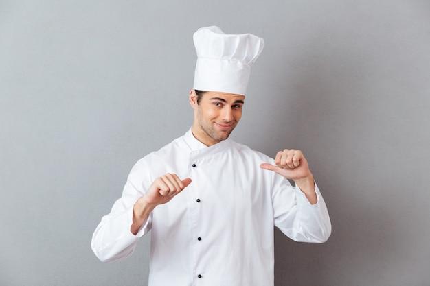 Красивый молодой повар в форме, указывая на себя. Бесплатные Фотографии