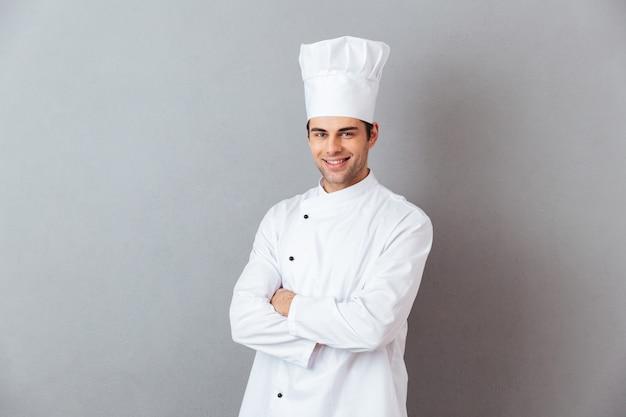Изображение веселый молодой повар в форме стоя, изолированных на серую стену Бесплатные Фотографии