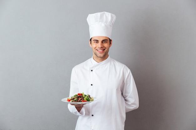 サラダを保持している制服を着た幸せな若い料理人。 無料写真
