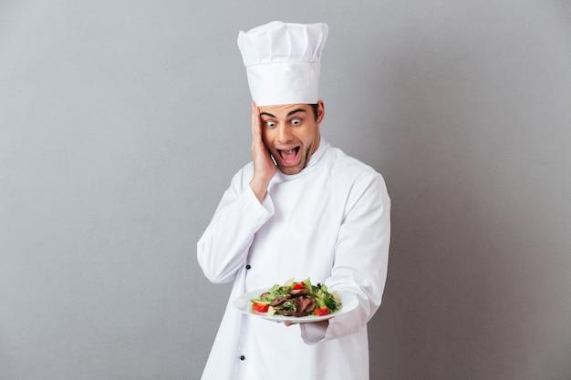 サラダを保持している制服を着た驚いて叫んで若いコック。 無料写真