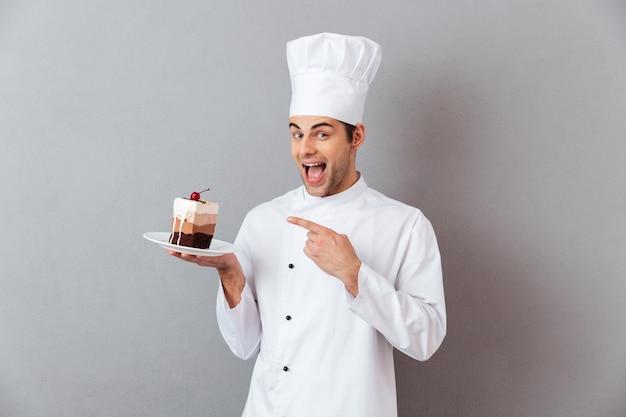Портрет веселый мужской шеф-повар, одетый в форму Бесплатные Фотографии