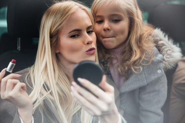 鏡を見て化粧をしている若いきれいな女性 無料写真