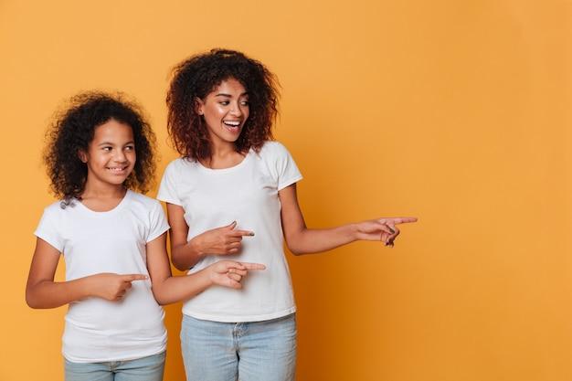 Портрет двух счастливых афро-американских сестер, указывая Бесплатные Фотографии