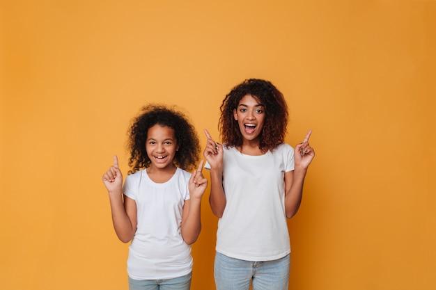 Портрет двух веселых афро-американских сестер, указывая пальцем Бесплатные Фотографии