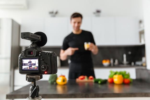 笑顔の男性ブロガーを撮影するビデオカメラのクローズアップ 無料写真