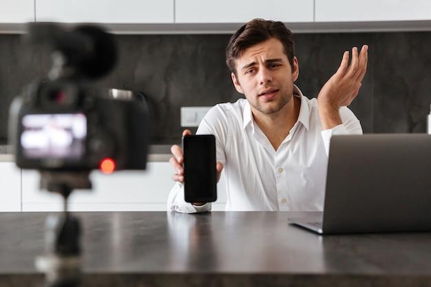 Красивый молодой человек снимает свой видео-блог Бесплатные Фотографии