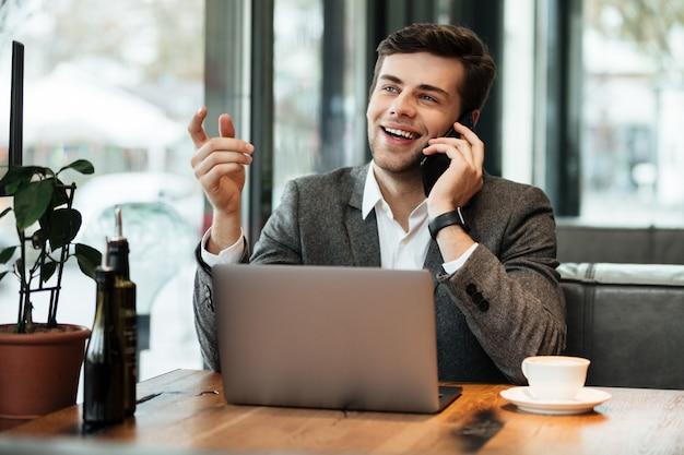 スマートフォンで話しながらノートパソコンとカフェのテーブルに座って幸せなビジネスマン 無料写真