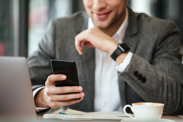 カフェのテーブルに座って、スマートフォンを使用して幸せなビジネスマンの画像をトリミング 無料写真