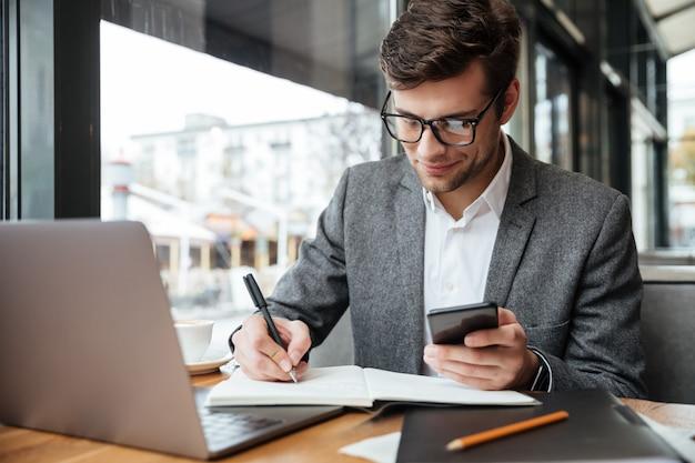 スマートフォンを使用して何かを書いている間ラップトップコンピューターでカフェのテーブルのそばに座って眼鏡のビジネスマンを笑顔 無料写真