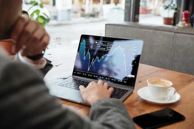 カフェのテーブルのそばに座って、インジケーターを分析する実業家の画像をトリミング 無料写真