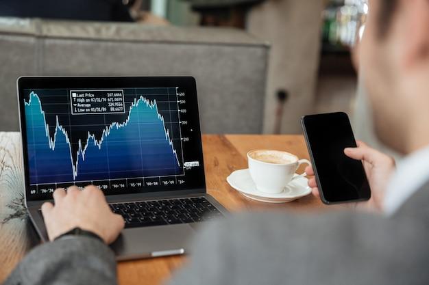 カフェのテーブルのそばに座って、スマートフォンを使用しながらラップトップコンピューターのインジケーターを分析する実業家の画像をトリミング 無料写真