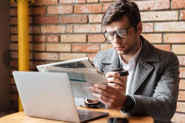 テーブルのそばに座って眼鏡で真面目な実業家 無料写真