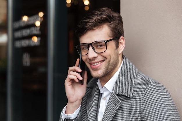 Улыбающийся бизнесмен в очках и пальто разговаривает по смартфону Бесплатные Фотографии
