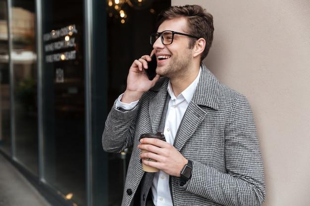 眼鏡とコートがスマートフォンで話している幸せなビジネスマン 無料写真