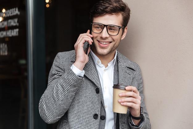 眼鏡とコートで話しているスマートフォンで満足している実業家 無料写真