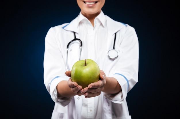 青リンゴを保持している医療ガウンの若い女性の写真をトリミング 無料写真