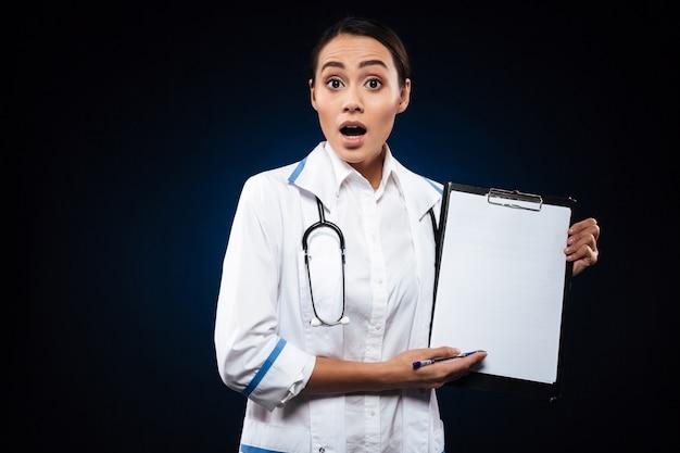Шокированный леди доктор в белом халате, показывая пустой буфер обмена изолированы Бесплатные Фотографии