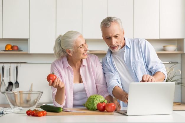幸せな成熟した愛情のあるカップル家族ラップトップを使用して、料理 無料写真