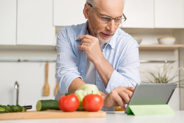 Сконцентрированный зрелый человек в очках готовит салат Бесплатные Фотографии