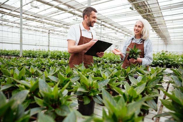 庭を見て、植物に触れる笑顔の労働者 無料写真