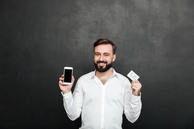 暗い灰色で分離されたオンラインショッピングのスマートフォンとクレジットカードを使用してカメラにポーズブルネットの男の肖像 無料写真
