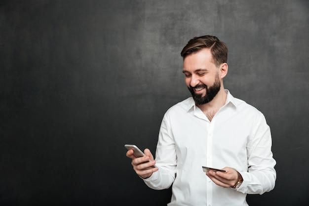 暗い灰色で分離された携帯電話とクレジットカードを使用してインターネットでオンライン支払いを行う陽気な男の肖像 無料写真